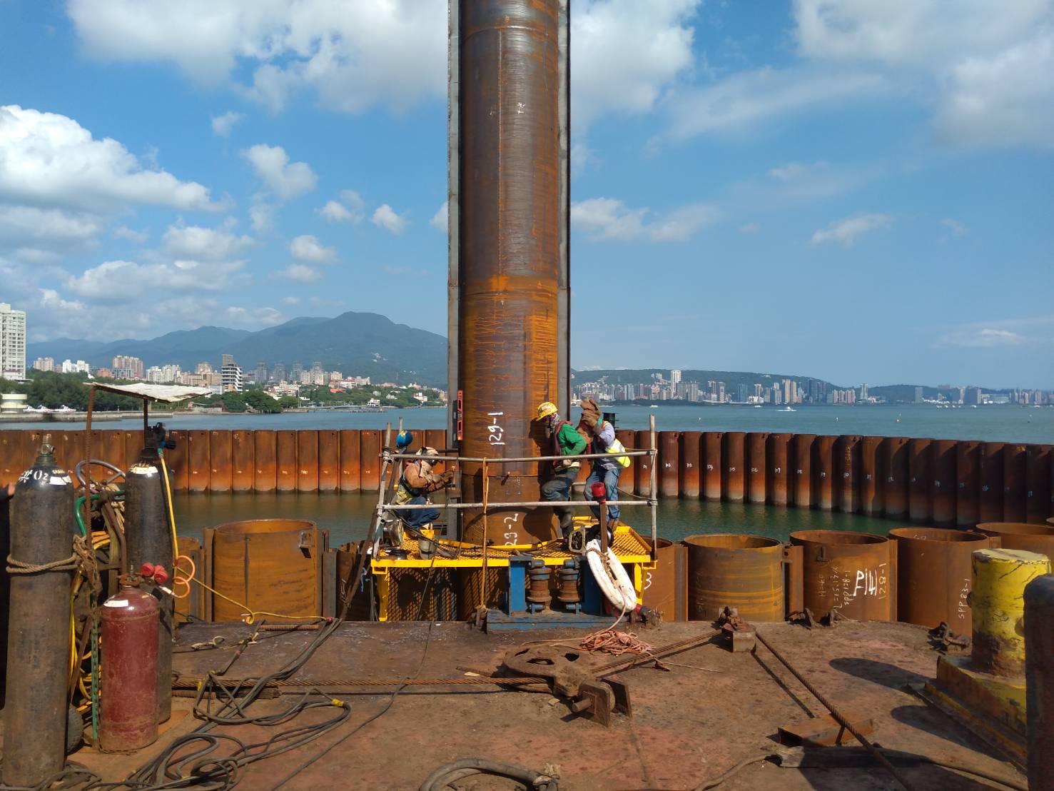 河中段圍堰鋼管樁垂直焊接作業.